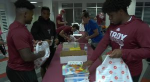 Trojan Football players help Short the Squirrel build reading kits for Children's Hospital patients.