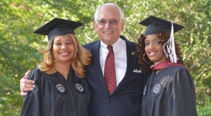 Pam Austin (left) and Michonda Austin pose with Chancellor Jack Hawkins Jr. before graduating at the Troy Campus.
