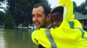 TROY graduate and former football player Tyler Parker helps a child to safety during flooding in Baton Rouge. (Image courtesy Tyler Parker)