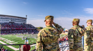 Members of the military salute during the national anthem at Troy University's Military Appreciation football game.