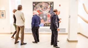 Visitors viewing some of the art on display as part of the Heritage Show, a collection of work by TROY art faculty past and present.