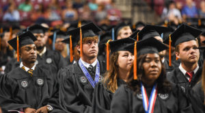 Troy Trojans quarterback Brandon Silvers listens to Congress Bill Johnson's address during Troy University's summer commencement in Trojan Arena.