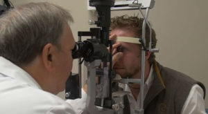 Dr. Robert Morris examines the eyes of Cameron Stovall, who lost his sight in a hunting accident. The two will speak at TROY's Helen Keller Lecture.