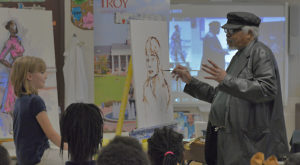 Artist Dr. Art Bacon paints a Troy Elementary School student during a live art demonstration sponsored by Troy University's International Art Center.