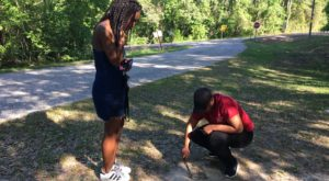 TROY students Mya Bell and Ciara Jones collect dirt in Perote, Alabama in memory of lynching victim Tobe McGrady.