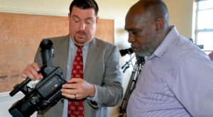 Aaron Taylor, TV production coordinator, shows one of the cameras donated to Booker T. Washington Magnet School broadcast teacher Richard Williams.
