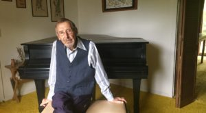 Carl Vollrath, music professor, sitting at his piano at home after discussing his opera with TROY Public Radio.