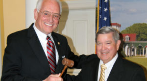 Fred C. Crawford presents the chairman's gavel to Dr. Jack Hawkins, Jr. during the Jan. 31 meeting of the American Village Trust's Board of Trustees..