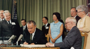 President Lyndon Johnson signs the Medicare bill in 1965. (Photo/White House)