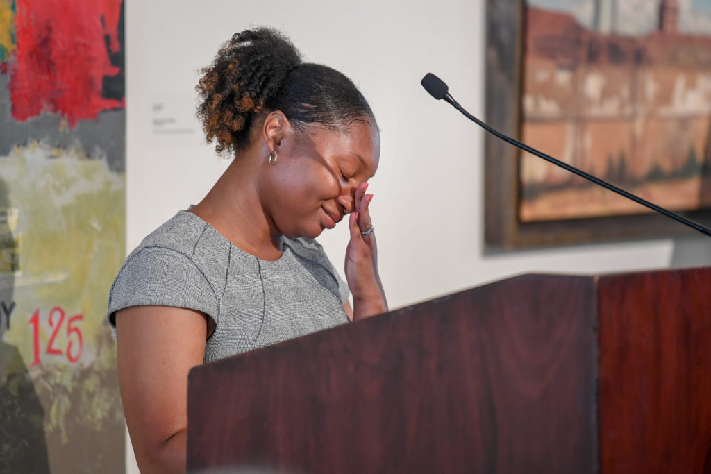 An emotional Jasmine Denson wipes her eyes while speaking behind a podium at the 2019 Trojan Heart awards ceremony in the Troy University International Arts Center.