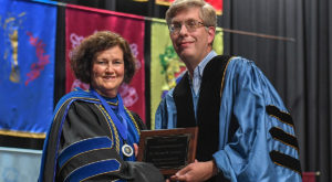 Dr. Theresa M. Johnson receives the Faculty Senate Excellence Award from Dr. Rob Kruckeberg, senate vice president.