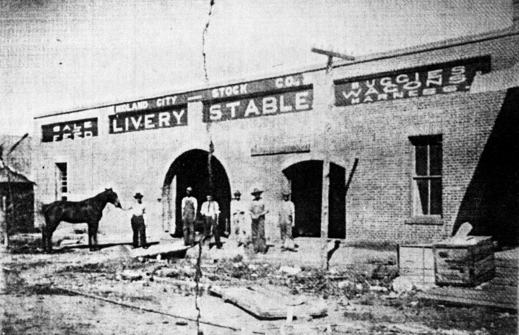 photo of Dr. Curtis Espy's livery stable, with a horse and several workers outside the building.