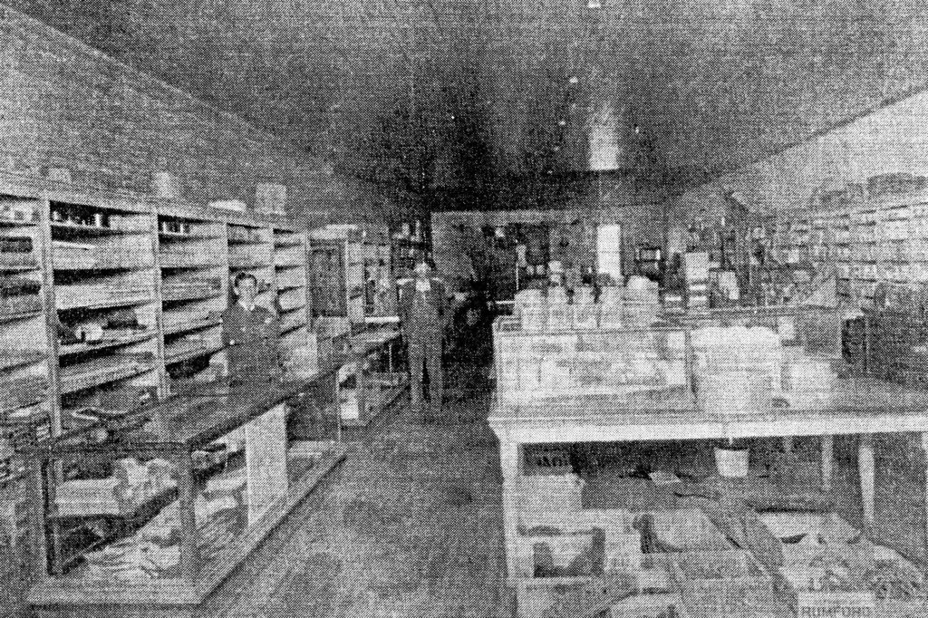 photo of Espy Mercantile circa 1908. A worker and a customer stand surrounded by goods and items.
