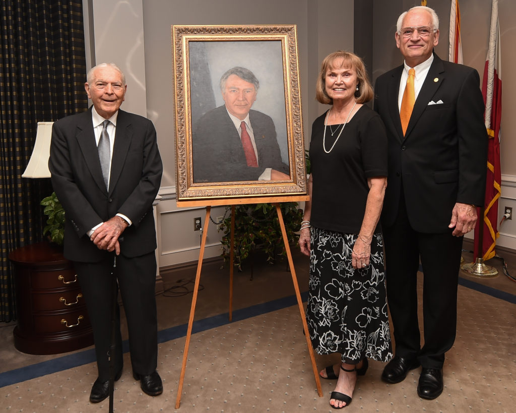 Rep. Terry Everett stands to the left of a new portrait in his honor inside the Michelin Room at Troy University's Dothan Campus. On the right side of the portrait, Barbara Everett and Chancellor Dr. Jack Hawkins, Jr., stand.