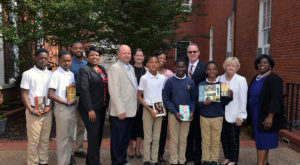Faculty from TROY's College of Education present books to scholars at Valiant Cross Academy as a part of the Warriors for Reading initiative.