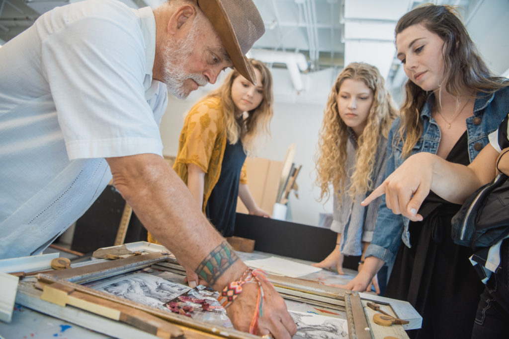 The artist Nall, left, works on a collaborative art piece alongside three female Troy University art students during Nall Day on May 7.