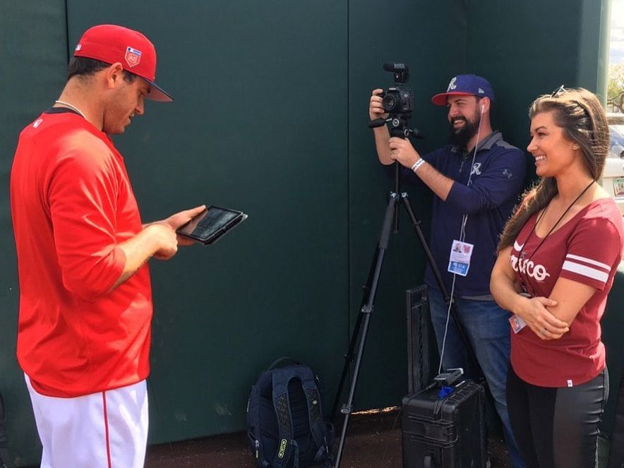 Melanie Newman, right, interviews a baseball player (far left) while a camera operator (center-right) looks on. The baseball player is looking at a video on a tablet.