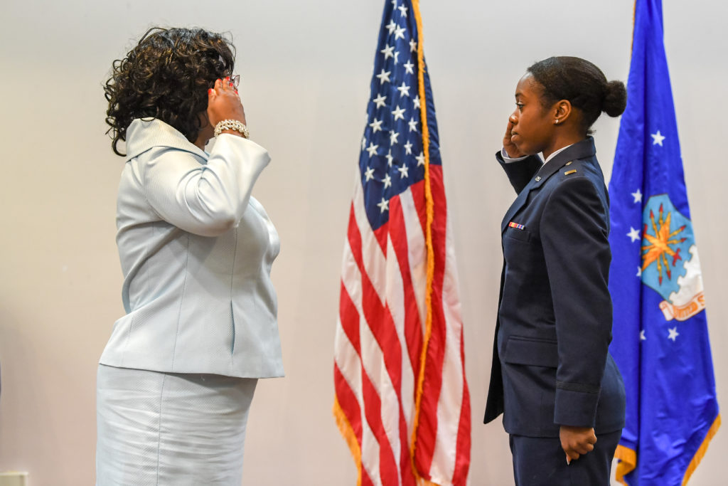 Christalyn Springs, right, wearing her Air Force uniform, salutes her mother, left, wearing a white blouse, who served 26 years in the Air Force. An American flag stands between them.