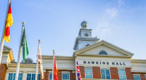 A photo of Flags flying outside of Hawkins Hall on the Troy Campus.