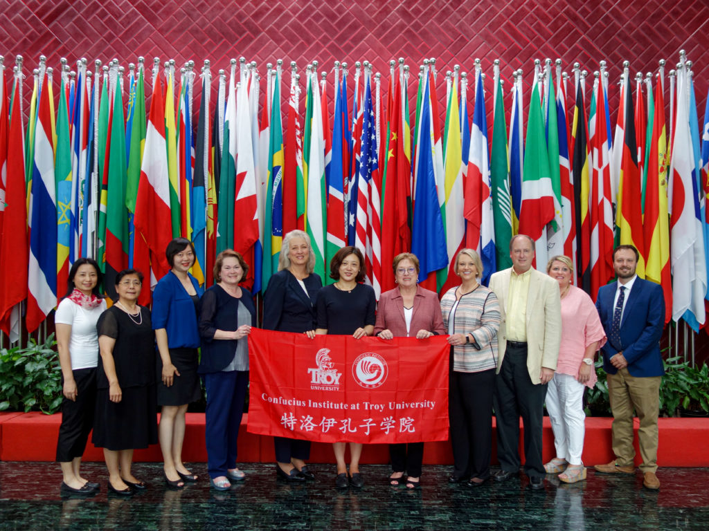 A group of Confucius Institute and Troy University representatives gather together behind a TROY Confucius Institute banner at Hanban, the Institute's headquarters in Beijing, China.