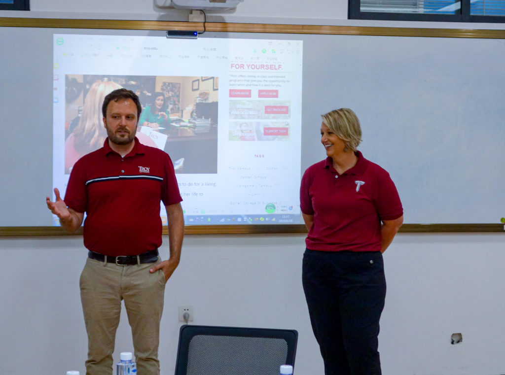 Troy University Director of Media Relations Matt Clower, left, and Assistant Professor of English Dr. Paige Paquette address a class at Chongqing Normal University. They stand in front of a whiteboard with a web page projected on it.
