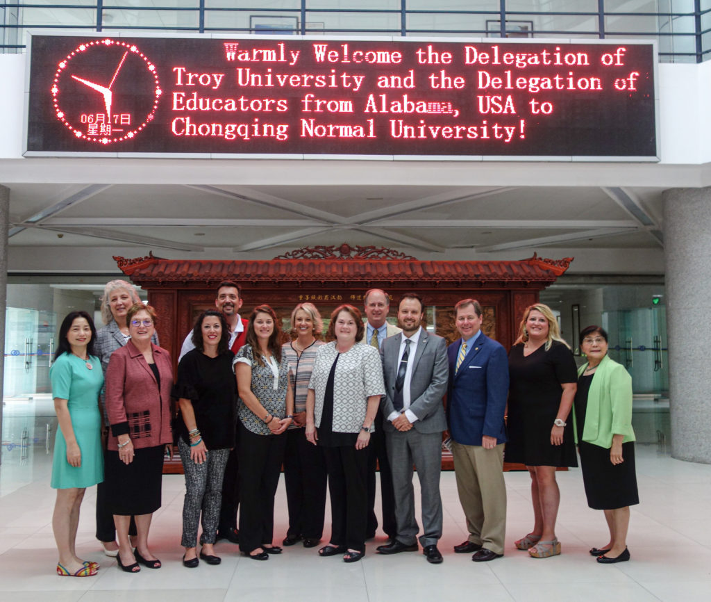 "A Troy University delegation poses at Chongqing Normal University in Chongqing, China. Above them, a digital billboard reads ""Warmly Welcome the Delegation of Troy University and the Delegation of Educators from Alabama, USA to Chongwing Normal University!"""