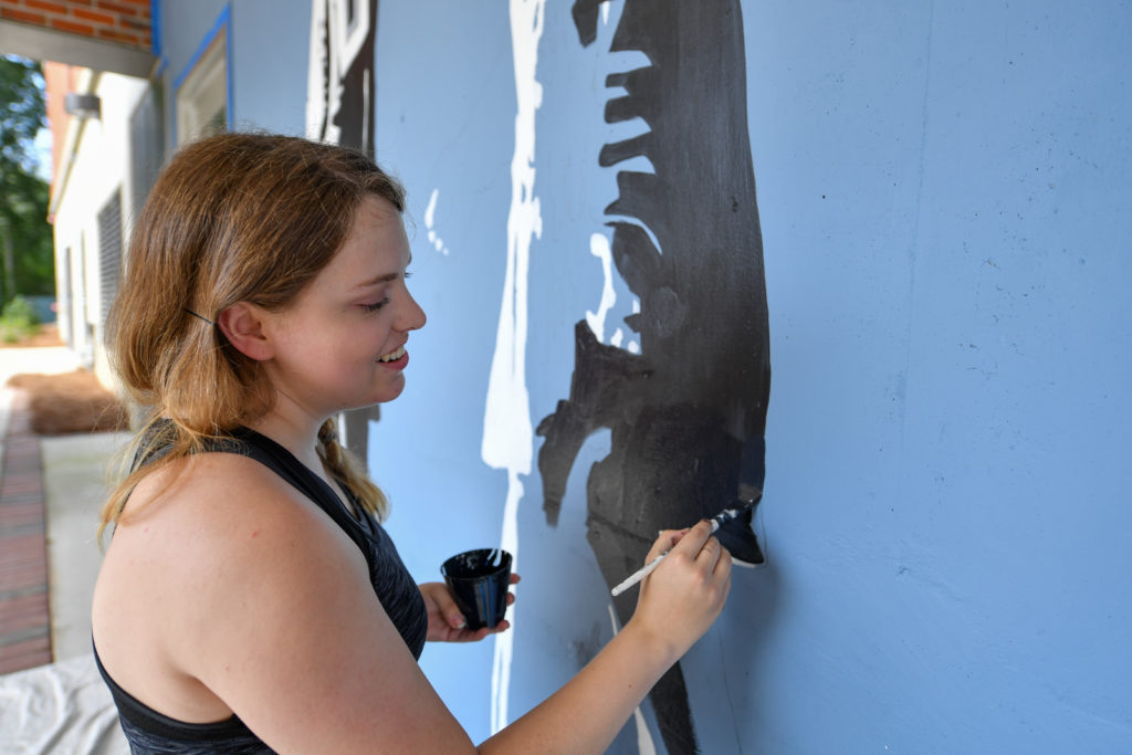 Sara Ivey holds a paint cup in her left hand while using her right hand to paint a mural at the International Arts Center in Troy.