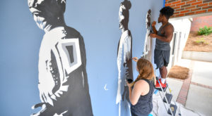 Alumni Sara Ivey and Karvarus Moore have given back to their university by painting a mural on the outside wall of the International Arts Center.