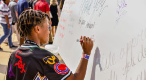 Community members had a chance to sign the TROY for Troops support board at Saturday's game, sending encouraging messages to service members.