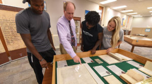 Dean of Library Services Dr. Chris Shaffer talks with students Zayvius Miller, Oliva Wright, III, and Cassidy Terrill about The Remnant Trust exhibit.