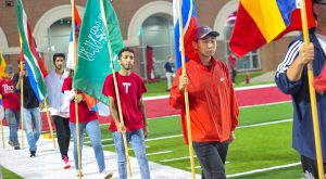International students at TROY carry flags from their home countries during the annual parade of flags prior to a recent Trojans' football game.