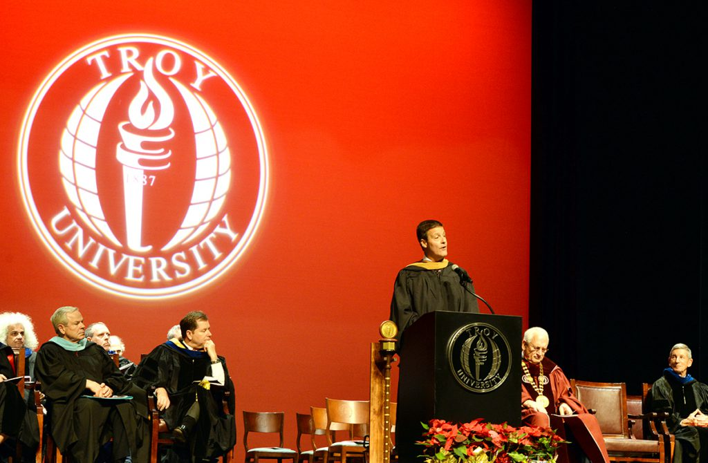 Jeff Coleman speaks behind a podium at commencement ceremonies at Troy University's Dothan Campus.