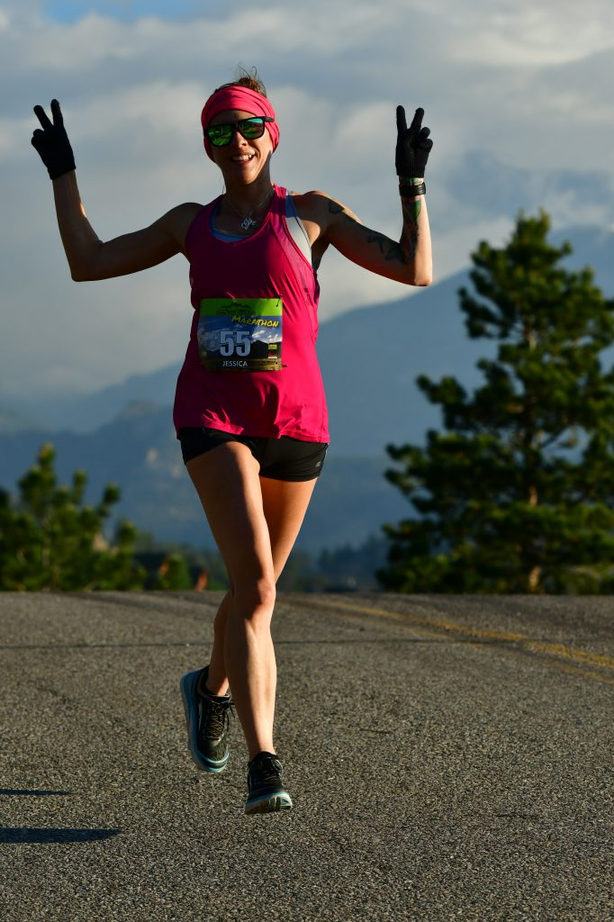 """Jessica Jones smiles and gives two """"peace signs"""" with her hands as she runs a marathon."""