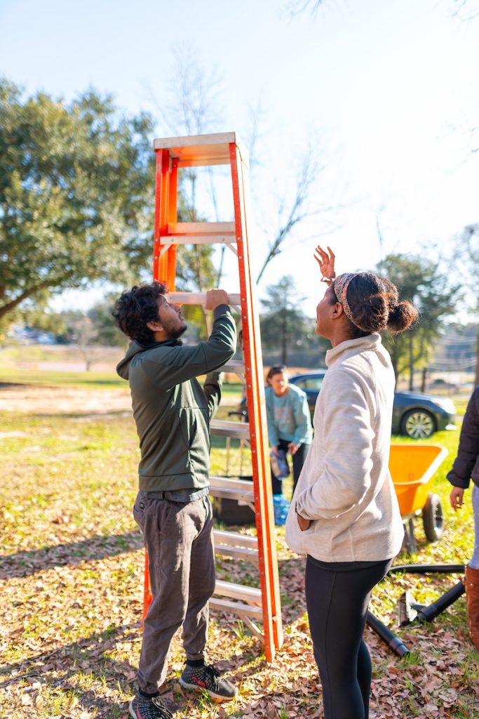 A TROY student holds a ladder during the MLK Days of Service.