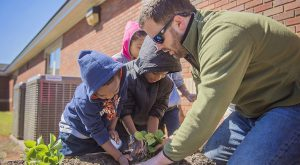 Jonathan Cellon, Associate Dean of First Year Studies, helps Troy Elementary students plant a garden as a part of a community garden project.