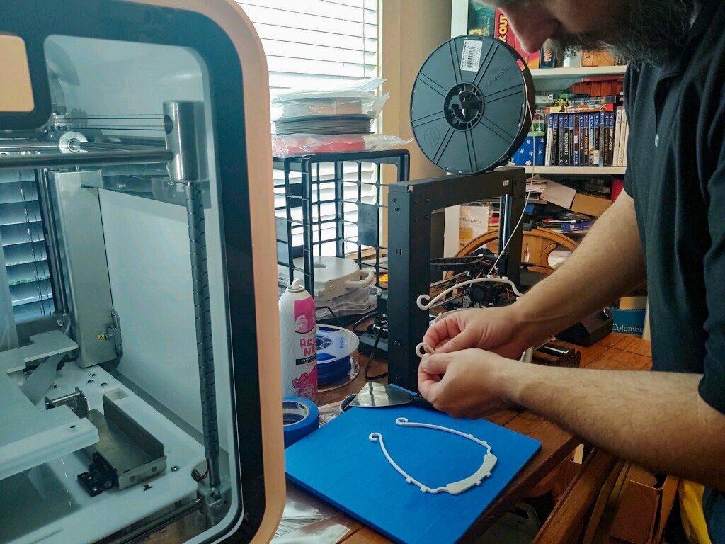 Jeff Herring displays his 3D printer as it makes PPE.