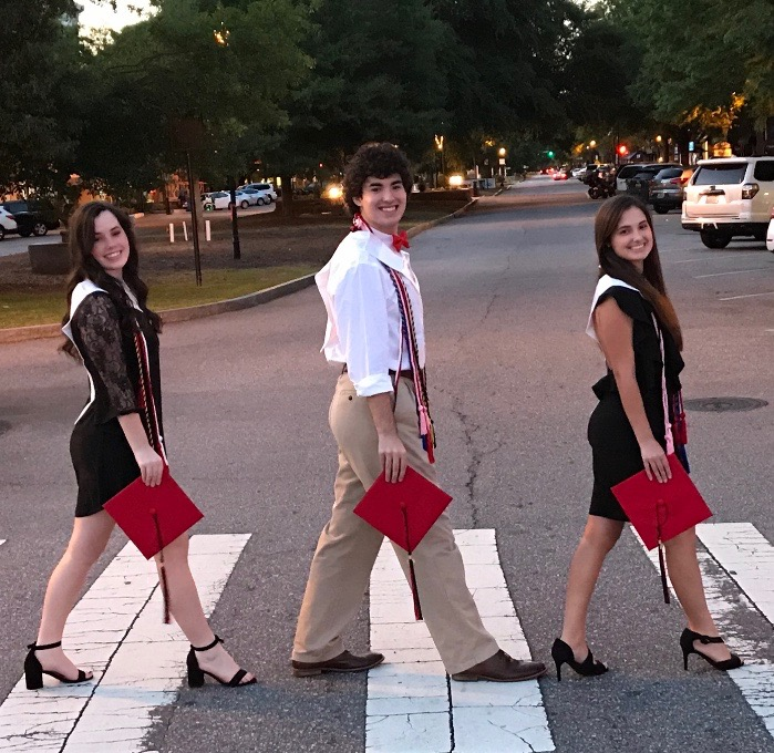 The Hornsby triplets recreate the album cover of the Beatles' Abbey Road, walking across a street holding their graduation caps.