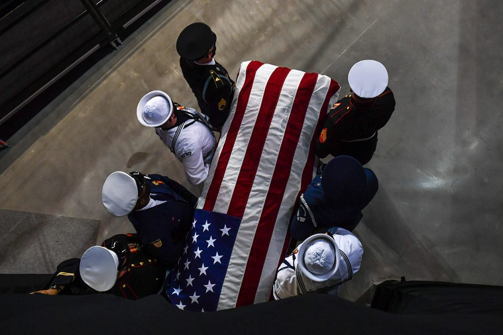 Military personnel escort the casket of John Lewis, which is covered in the American flag.