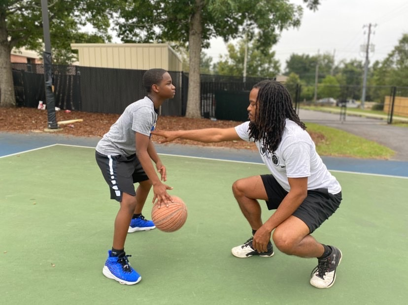Aaron Allen works with a young student on his basketball skills.