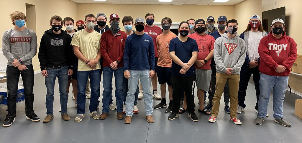 A contingent of men from Troy University's IFC fraternities pitched in to help the McClaney Foundation package holiday food for needy families. (photo submitted)