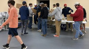 Members of various fraternities at Troy University joined together to help the McClaney Foundation prepare holiday food boxes for families in need.