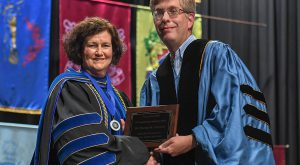 Dr. Kruckeberg presents the Faculty Senate Excellence Award to Dr. Theresa M. Johnson during the 2019 Honors Convocation.