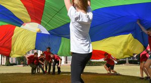 Home school students take part in pararchute activity on the Troy Campus as a part of a physical education program developed by Lana Johnson.