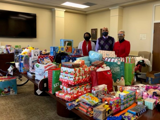 Phenix City Vice Chancellor Dr. Dionne Rosser-Mims (Left), Phenix City Housing Authority Director Dr. Jason Whitehead (Center), and Regional Director for Development Kathy Ninas (Right) pose with Adopt-a-Family 2020 donations in the riverfront campus boardroom.