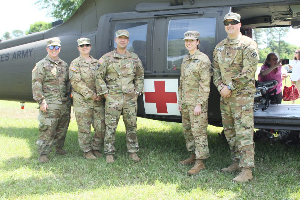 Five Soldiers pose next to a medevac helicopter during Armed Forces Day at the TROY Dothan Campus.