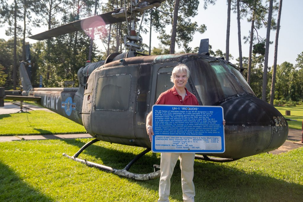 Maj. Gen. Walter Givhan (Ret) holds the sign of the UH-1 Iroquois before the helicopter is taken on the road.