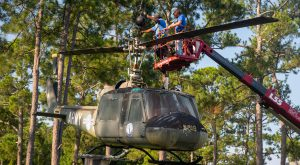 Workers set a crane to remove the UH-1 Iroquois from its display (photo/Jonathan Sellers)