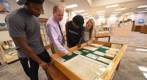 Dr. Chris Shaffer, Dean of Library Services, and students examine the 2019 exhibit from The Remnant Trust collection. A new exhibit will begin Aug. 26