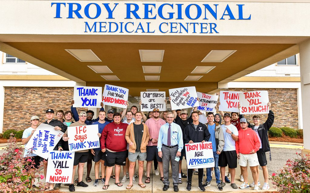 FarmHouse fraternity brothers and hospital administration stand out front of the medical center Monday morning.