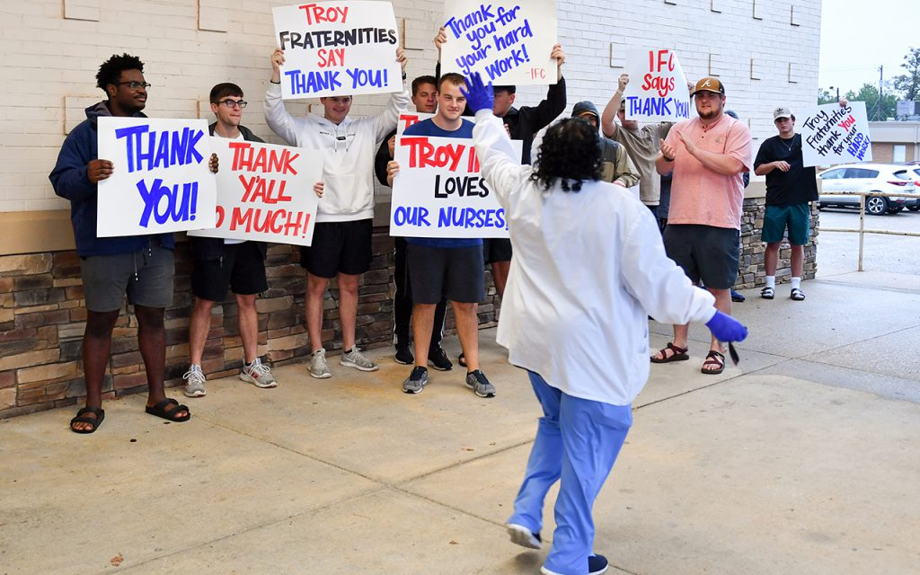 A TRMC employee waves to members of FarmHouse as she leaves from the emergency department.